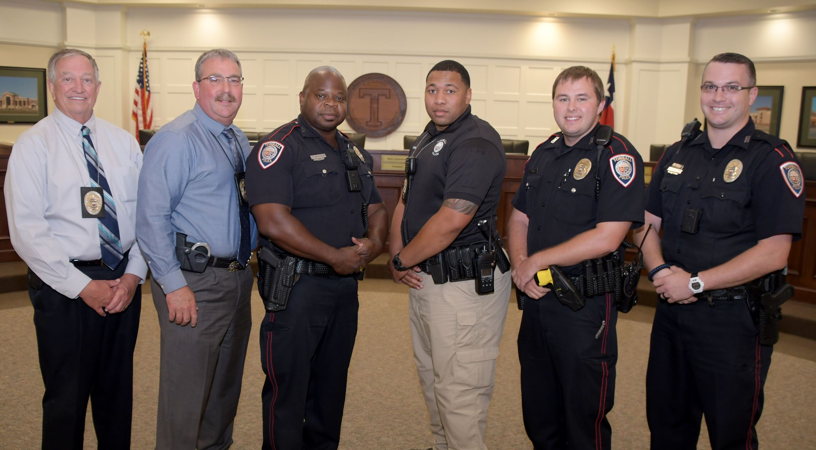 SRO Team image taken at Tomball ISD board room showing six standing men. From left to right, Chief B